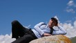 Happy traveler resting on stone in Tian Shan mountains, Kyrgyzstan