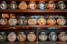 Closeup Shot Of Nicely Arranged Jars On A Wooden Shelf Filled With Traditional Japanese Biscuits And Candies, Tokyo, Japan