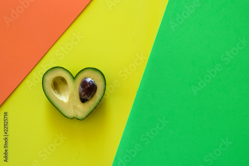 Heart-shaped avocado on colorful background