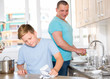 Man with his son are washing dishes on the kitchen