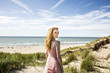 Netherlands, Zandvoort, portrait of smiling woman standing in dunes