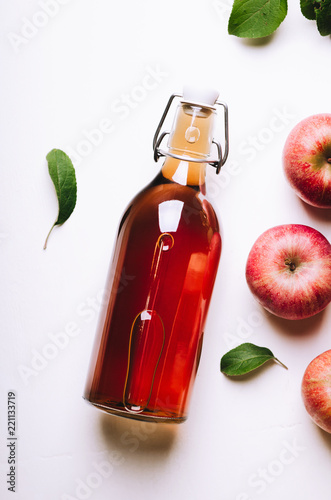 Apple vinegar in a bottle on white wooden table with apples and leaves. Rustic style. Top view.