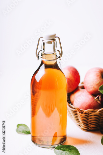 Apple vinegar in a bottle on white wooden table with apples in a basket.
