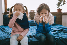 Being Ill. Depressed Young Girls Using Paper Tissues While Being Sick
