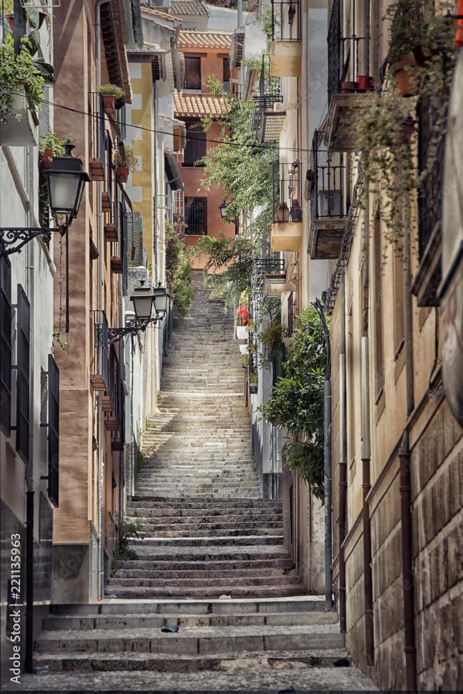 Fototapeta Old street with stairs in Granada in Spain.