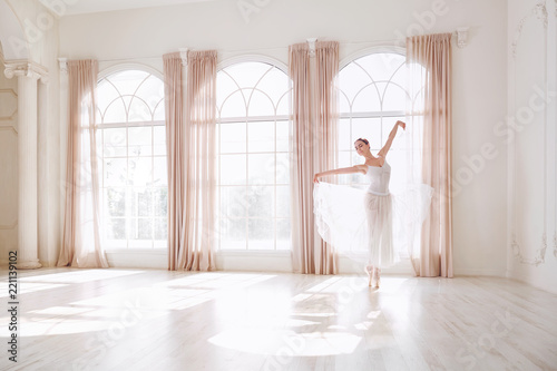 Fotografie, Tablou  Ballerina dancing in a studio on white background window.