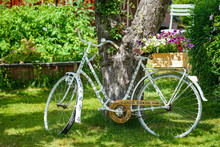 Picture Of Old Vintage Bicycle With Flowers On The Green Grass