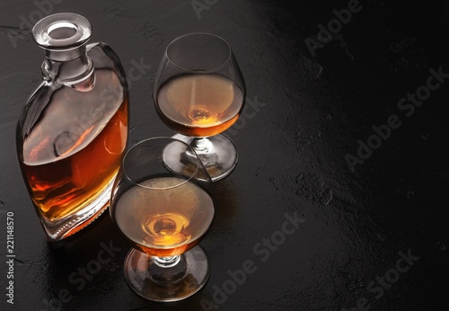 Tela Two glasses of brandy or cognac and bottle on black