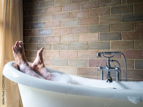 Valokuvatapetti Men's  feet covered with foam bubble bath  in luxury bathtub with happiness and