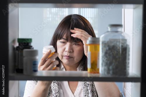 Carta da parati Woman looking at prescription drugs in her medicine cabinet