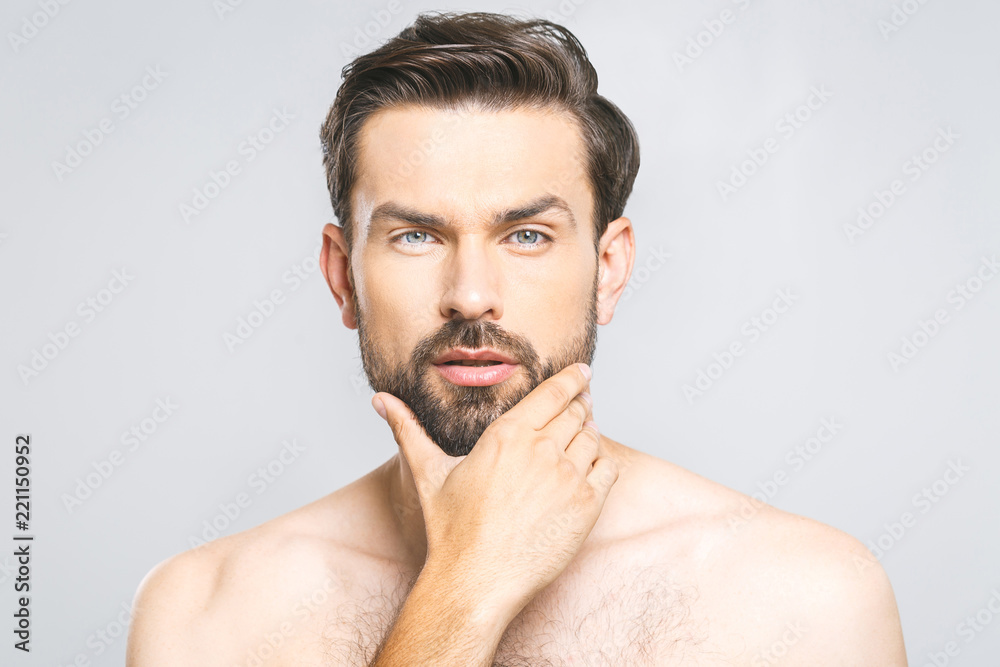 Fototapeta Photo of young man standing isolated over grey wall background naked. Skincare concept.