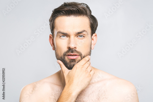 Photo of young man standing isolated over grey wall background naked. Skincare concept.