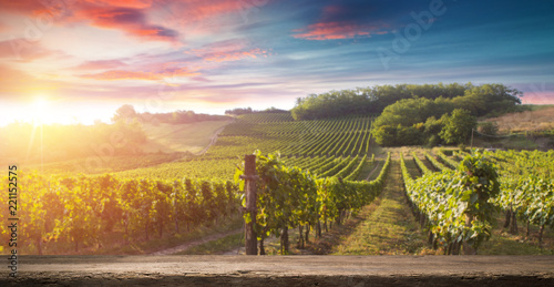 Spoed Fotobehang Wijngaard Red wine bottle and wine glass on wodden barrel. Beautiful Tuscany background