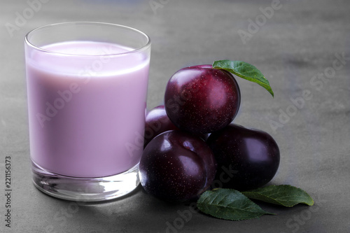 Fototapeta yoghurt from plum and fresh ripe plums with leaves on a gray background. close-up obraz