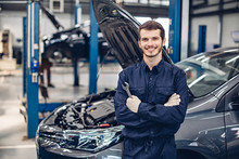 Auto Car Repair Service Center. Happy Mechanic Standing By The Car