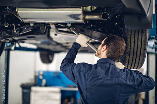 Fototapeta Auto car repair service center. Mechanic examining car suspension obraz