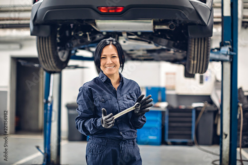 plakat Auto car repair service center. Happy female mechanic standing by the car