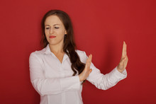 Body Language. Disgusted Stressed Out Angry Beautiful Young Woman Posing At Studio Wall, Keeping Hands In Stop Gesture, Trying To Defend Herself As If Saying: Stay Away From Me