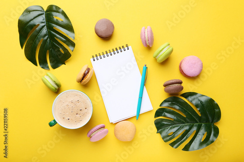 Notebook with colorful macarons and monstera leafs on yellow background