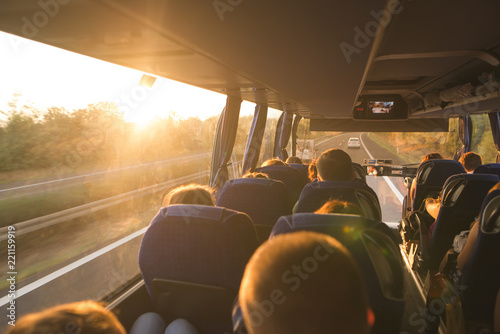 Obraz Background. Travel by bus. Bus interior. Salon of the bus with people fill the sun with light in the sunset. People travel on a big tourist bus. The bus rides along the mornings in the sunrise - fototapety do salonu