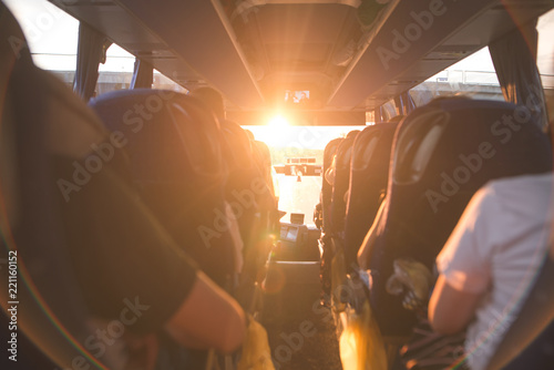 Background, bus interior. The salon of the bus with people fill the sun with light in the sunset. People travel on a big tourist bus. The bus rides along the mornings in the sunrise