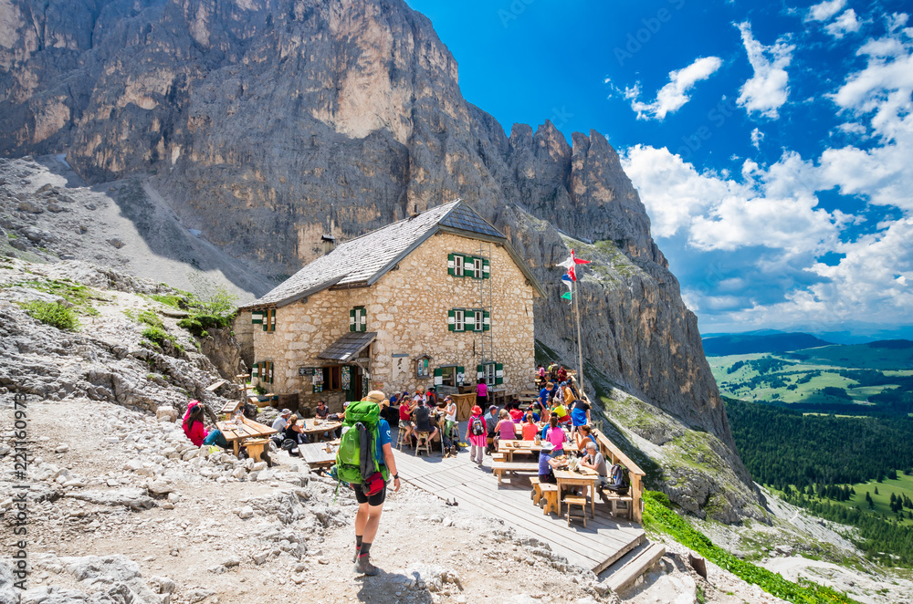 Fototapety, obrazy: RIFUGIO VICENZA, SASSOLUNGO MASSIF, ITALY, JULY 1, 2018: Mountaineering people resting at Vicenza chalet in Dolomites mountains.