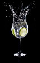 Gin Tonic Cocktail Splashing Isolated On Black Background