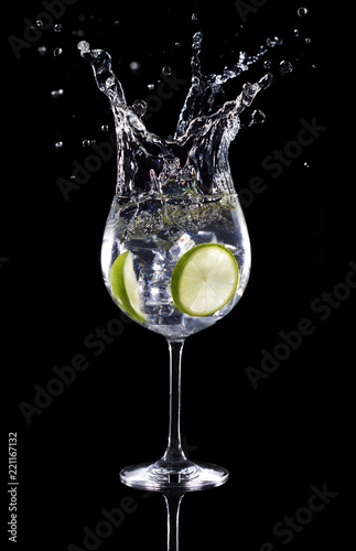 Poster Cocktail gin tonic cocktail splashing isolated on black background