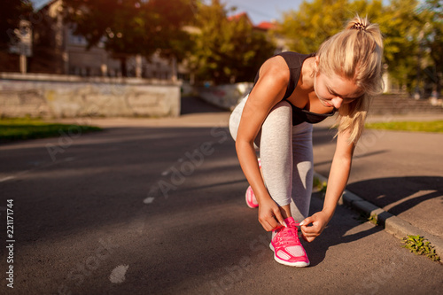 Fotografía  Young woman athlete tying sneakers on running track on sportsground in summer