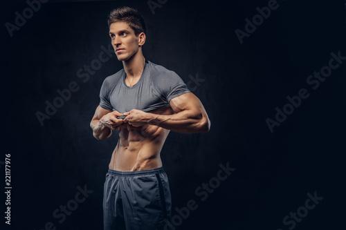 Fotografie, Obraz  Stylish ectomorph bodybuilder with stylish hair takes off his shirt on the dark background