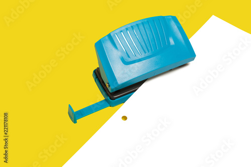 Fotografia, Obraz  Blue plastic modern new office hole puncher lying with a paper isolated on a yellow background