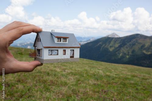 Zdjęcie XXL Marzysz o domu. Ręka trzyma wzorcowego dom w zielonym wzgórzu