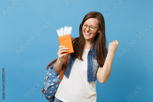 Fotografía  Young overjoyed woman student in glasses with backpack hold passport, boarding pass tickets clenching fist like winner or happy human isolated on blue background