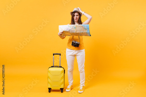Fotografie, Obraz Traveler tourist woman in summer casual clothes, hat with suitcase, city map isolated on yellow orange background