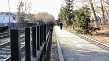 People Walking Along Path Bordering Train Tracks On A Winter Day