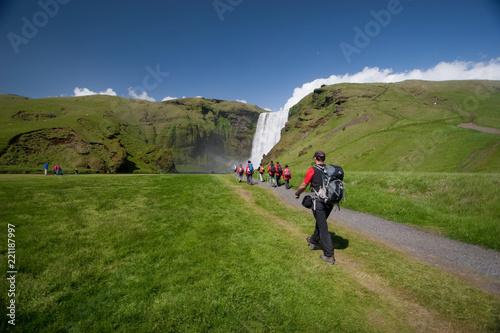 Grupo de personas caminando hacia la cascada de Skógafoss en Islandia Canvas Print