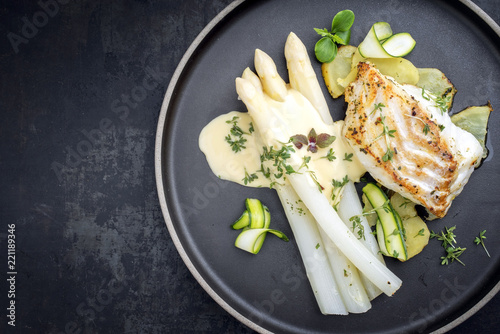 Modern German fried cod fish filet with white asparagus in hollandaise sauce with roast potatoes and sliced zucchini as top view on a plate with copy space left