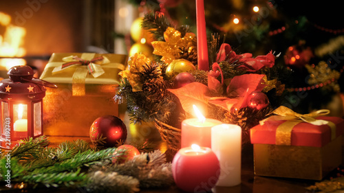 Closeup image of burning candles in traditional wreath against Christmas tree and fireplace