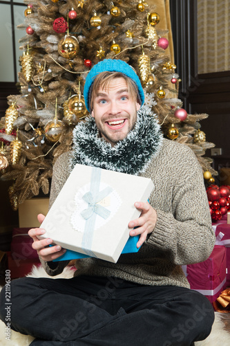 3624b5766e580 Happy man with gift box sit at Christmas tree - Buy this stock photo ...