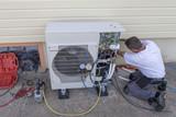 Fototapeta Dmuchawce - heat Pump. plumber at work installing a circulation heat pump