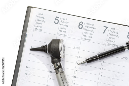 Photo Doctor Agenda. Otoscope and pen lyinhg on agenda after exam
