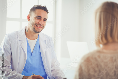 Fotomural  Handsome doctor is talking with young female patient and making notes while sitting in his office