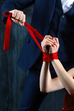 Couple In Dating. Body Rich Man Male Tying Woman Hands. Woman Female In Expensive Red Evening Dress With Tied Hands By Red Tie On Dark Background. Henpecked Violence Issue Relationship Concept.