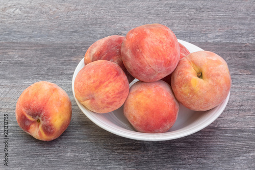 Fresh, ripe peaches in white bowl, on wooden background