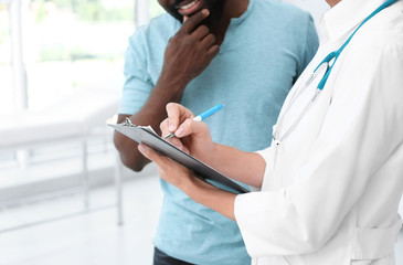 Young doctor consulting African-American patient in hospital