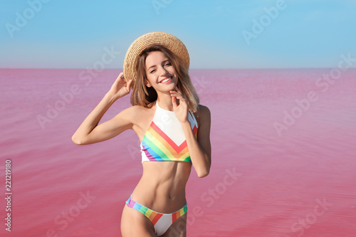 Wall Murals Candy pink Beautiful woman in swimsuit posing near pink lake on sunny day