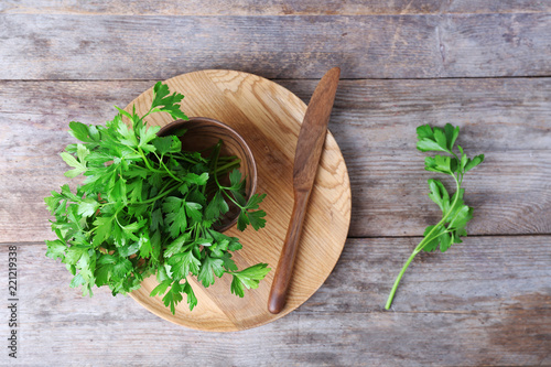 Flat lay composition with fresh green parsley on wooden background