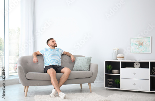 Fotografie, Obraz  Young man relaxing under air conditioner at home