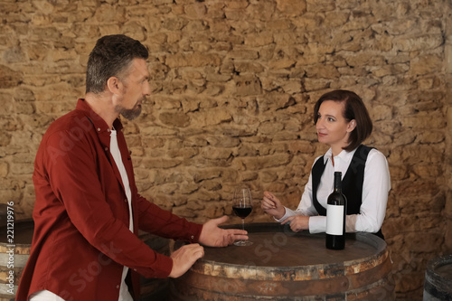 Waitress serving glass of red wine to client in restaurant