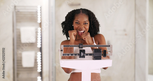 Fotomural  Cute smiling black female stands on weight scale cheering weight loss
